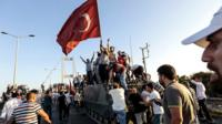 People standing on a tank with a Turkish flag