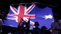 School children march with an Australian flag in the Australia Day Parde on January 26, 2014