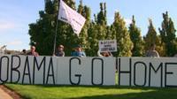 Protestors hold an 'Obama go home' sign