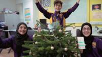 Three children stood around a Christmas tree with their arms in the air, looking happy.