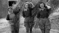 Land Girls carrying bundles of straw in 1941.