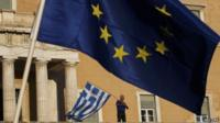 A protester waves a Greek flag at the entrance of the parliament building in Athense