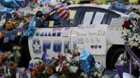 Notes, flowers and other items decorate a squad car at a make-shift memorial in front of the Dallas police department - July 9, 2016