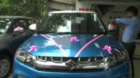 New car adorned with pink ribbons