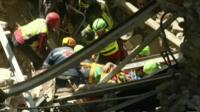Man on stretcher being removed from destroyed building in Accumoli