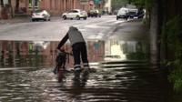 Cyclist walks through a puddle