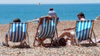 Sunbathers enjoying warm weather on the beach.
