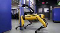 SpotMini robot opening a door