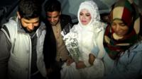 Syrian woman wearing wedding dress surrounded by husband to be and friends