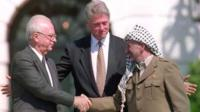 US President Bill Clinton standing between PLO leader Yasser Arafat as he shakes hands with Israeli Prime Minister Yitzhak Rabin