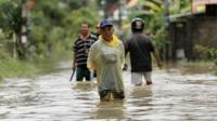 People walk in a flooded street at Muang district in Nakhon Si Thammarat Province, southern Thailand, 6 January 2017