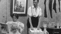 A woman reading a magazine while a man washes the laundry