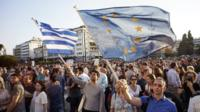 Demonstrators waving Greek and EU flags