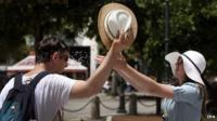 Man being cooled down with water and sunhat