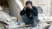 A Syrian man sitting on top of rubble in Aleppo