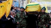 Hezbollah members carry the coffin of Mustafa Badreddine