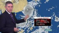 BBC Weather presenter Philip Avery stands in front of a satellite chart showing the progression of Typhoon Megi.