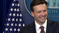 Press secretary Josh Earnest smiles as he speaks to journalists