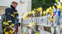 Firefighter at floral tributes near Grenfell Tower