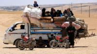 Syrians, who fled the Islamic State (IS) group stronghold of Raqqa, ride with their belongings on a truck, in an area near the village of Balaban, south of Jarablus, Syriaemb