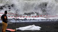 A policeman stands next to the body of a body-boarder killed by a shark, covered by a white cloth next to his body-board on 21 February 2017 on a beach in Saint-Andre, on the French island of Reunion in the Indian Ocean