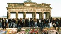 Germans from East and West standing on the Berlin Wall in front of the Brandenburg Gate
