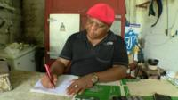 man writing in ration book