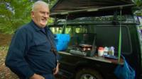 Michael Sanderson cooks food from a hob attached to the side of his car