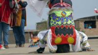 A scissor dancer balances on his head
