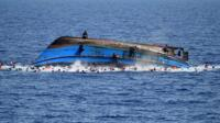 A trawler carrying hundreds of migrants overturned in the Mediterranean - apparently as a result of people rushing to one side after spotting a rescue ship.