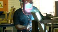 Zandile Dlamini at work with a welding helmet as sparks fly off the chassis