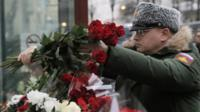 A Russian soldier places flowers at a small memorial outside the home stage of the Alexandrov choir in Moscow, Russia, 26 December 2016