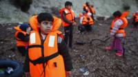Migrant children wearing life jackets wait for a dinghy to sail off for the Greek island of Lesbos from the Turkish coastal town of Dikili
