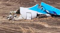 A handout picture from the Russian Emergency Ministry shows Russian Emergency Situations Minister Vladimir Puchkov (4-L) and unidentified officials near a piece of wreckage of Russian MetroJet Airbus A321 at the site of the crash in Sinai