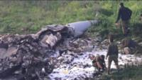 Men inspect the site of the crashed jet