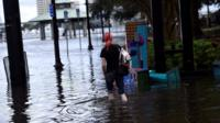 Woman walking in Florida floodwaters