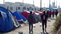 """Migrants walk in the northern area of the camp called the """"Jungle"""" in Calais,"""