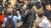 Dominique Strauss-Kahn surrounded by reporters in Paris