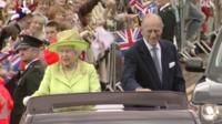 The Queen and Prince Philip in an open-topped vehicle