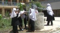 Afghan schoolgirls use a water well