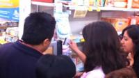 People using a prepaid card in a supermarket