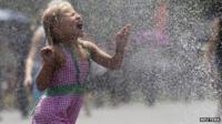 A girl runs through a water fountain Washington DC 5 July 2012