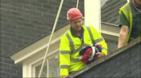 Downing Street worker carries the union jack that was taken down to make way for the Scottish Saltire