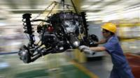 An employee pushes a car engine at a Geely Automobile assembly line in Cixi, China
