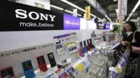A customer looking at Sony's portable music players displayed at an electronic store in Tokyo