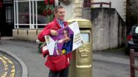A postman holds an 'Andy Murray stamp' beside the gold post box in Dunblane