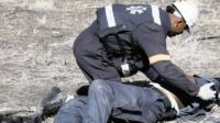 An injured policeman is attended to after he was attacked and injured by striking Lonmin miners near Rustenburg.