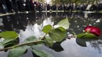 A flower lays on the memorial to the estimated half million Roma and Sinti murdered by the Nazis during World War II, in Berlin