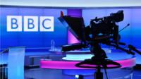 Silhouette of camera against Newsnight studio and BBC logo