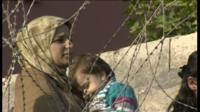 Woman and child by barbed wire fence